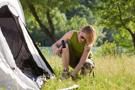 knees bent: Young woman fastening tent and holding hammer