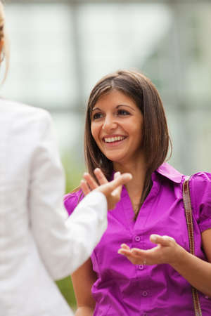 two mid adult business women talking outdoors. photo