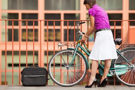 bicycle race: rear view of business woman locking padlock to her bike. Copy space Stock Photo