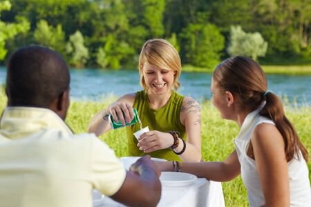 multi ethnic group having picnic outdoors and laughing photo
