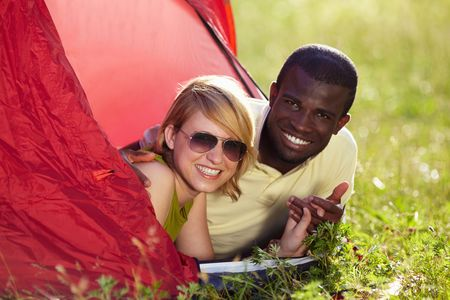 young multiethnic couple lying in tent and holding hands.  photo