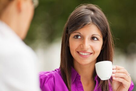 women holding cup: two business women drinking coffee outdoors