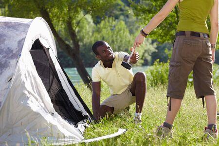 knees bent: Giovane afro-americano e uomo di fissaggio tenda azienda martello Archivio Fotografico