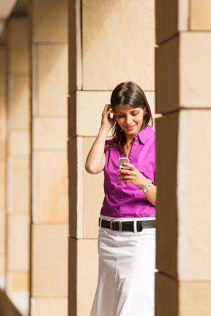 young adult businesswoman reading phone message on mobile phone. Copy space photo