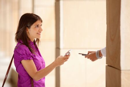 young adult businesswoman exchanging data with colleague�s mobile phone via bluetooth. Copy space photo