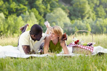 picnicking: portrait of young multiethnic couple picnicking in park Stock Photo