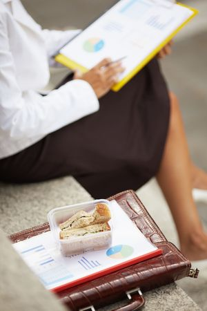 cropped view of business woman eating sandwich outdoors. Selective focus on sandwich photo