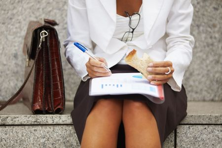 cropped view of business woman eating sandwich outdoors. Selective focus on hand and pen photo