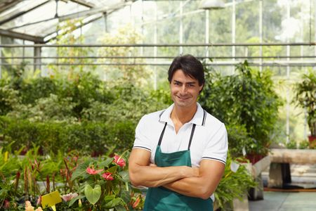florists: portrait of male florist looking at camera with arms folded