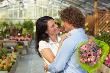 mid adult couple: mid adult couple hugging in flower nursery and holding bouquet  Stock Photo