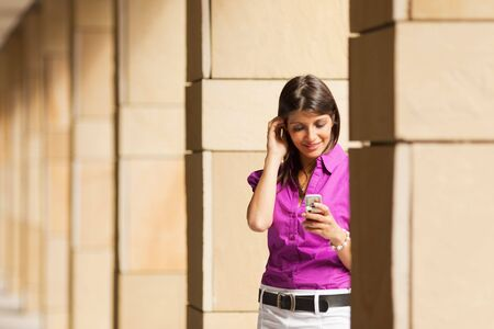 young adult businesswoman reading phone message on mobile phone. Copy space Stock Photo - 5104618