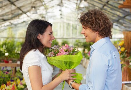 mid adult couple in flower nursery holding bouquet and looking each other photo