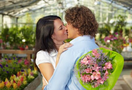 mid adult couple: mid adult couple kissing in flower nursery and holding bouquet