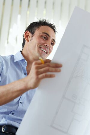 architect office: portrait of mid adult architect reading blueprint and smiling