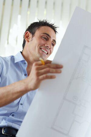architect: retrato de mediados de adultos arquitecto plan de lectura y sonriente