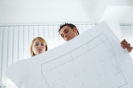 two architects examining blueprint indoors. Low angle view. Copy space photo