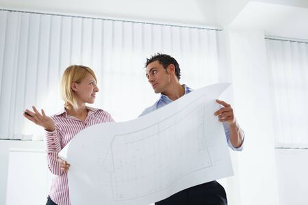 two architects examining blueprint indoors. Copy space photo