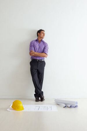 adult wall: portrait of mid adult architect leaning on wall and looking away. Copy space
