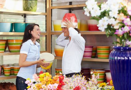 silliness: mid adult couple playing with flowerpots in flower shop