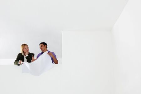 low angle view of male architect and woman examining blueprints. Copy space Stock Photo - 5168783