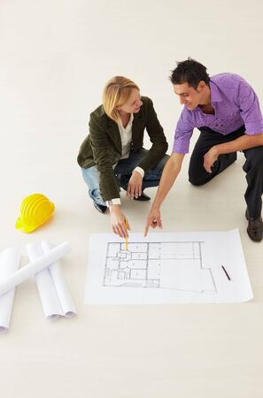high angle view of male architect and woman examining blueprints. Copy space photo