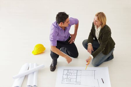 high angle view of male architect and woman examining blueprints. Copy space Stock Photo - 5168784