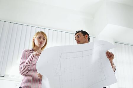 two architects examining blueprint indoors. Low angle view. Copy space Stock Photo - 5168787