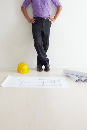 cropped view of mid adult architect leaning on wall and blueprints on floor. Copy space Stock Photo - 5168789
