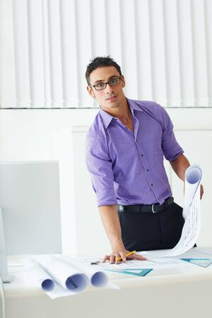 portrait of mid adult architect leaning on desk and looking at camera photo