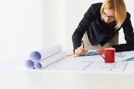 portrait of female architect drawing line on blueprint. Copy space photo