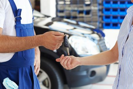 motor mechanic: cropped view of mechanic giving car keys to female client
