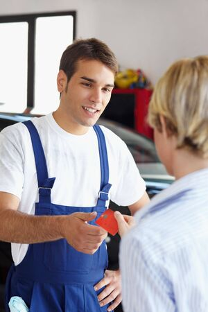 Rear view of woman giving credit card to mechanic. Stock Photo - 5192089