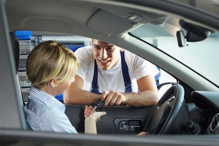 mechanic giving car keys to client sitting in car photo