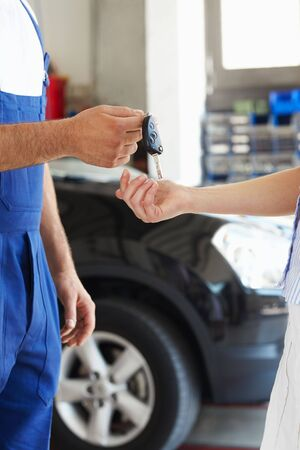 cropped view of mechanic giving car keys to female client Stock Photo - 5204892
