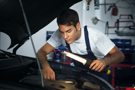 bonnet up: mechanic looking to car engine and holding lamp