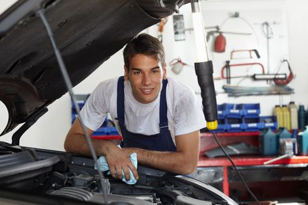 bonnet up: mechanic leaning on bonnet and looking at camera