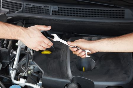 close up  wrench: close up of two mechanics sharing metal spanner. Stock Photo