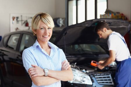 portrait of female client with arms folded in auto repair shop.