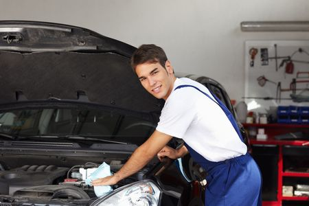 engine bonnet: mechanic cleaning car engine and looking at camera Stock Photo