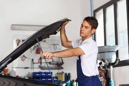 bonnet up: Male mechanic opening car bonnet. Side view