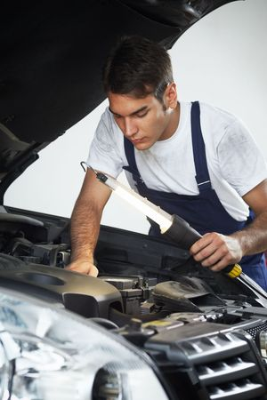 shop skill: mechanic looking to car engine and holding lamp