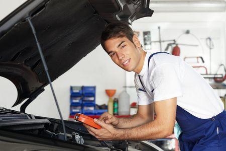 auto monteur: monteur leunend op de motorkap met tester apparatuur en kijkt naar camera