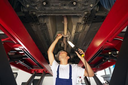 mechanic standing under car engine and holding lamp. Copy space Stock Photo - 5216642