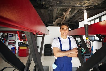portrait of mechanic standing under car with arms folded. Copy space photo