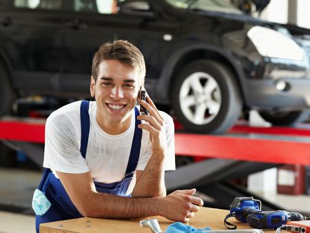 car in garage: portrait of mechanic talking on mobile phone in auto repair shop. Looking at camera
