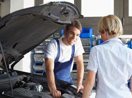 engine bonnet: mechanic talking with female client in auto repair shop.
