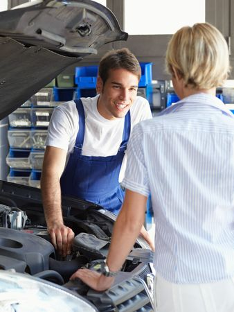 shop skill: mechanic talking with female client in auto repair shop.