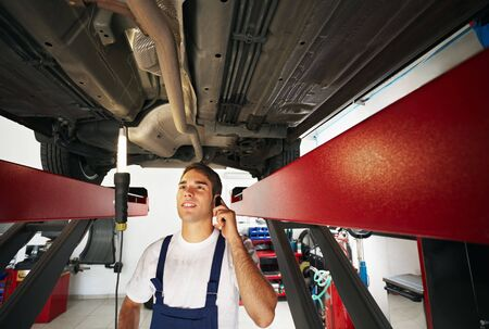 mechanic: mechanic standing under car engine and talking on mobile phone. Copy space