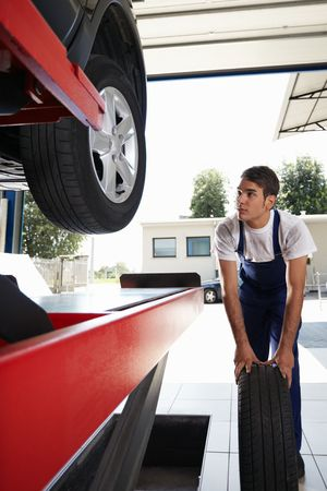 replacing: mechanic replacing car tyre in auto repair shop. Front view Stock Photo