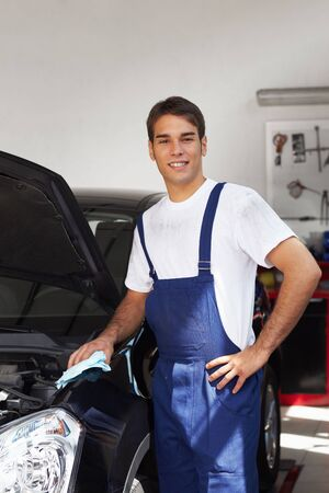 overalls: mechanic cleaning car engine and looking at camera. Copy space